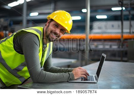 Portrait of factory worker using laptop at drinks production factory