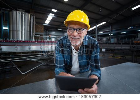 Portrait of factory worker using digital tablet at drinks production factory