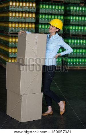 Tensed female worker standing with back pain in factory