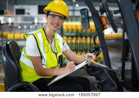 Portrait of female factory worker sitting on forklift and writing in clipboard at factory