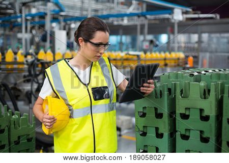 Attentive female factory worker using a digital tablet in factory