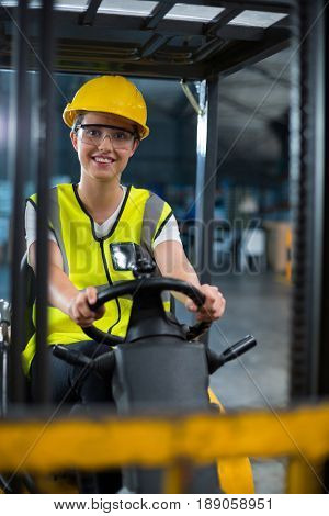 Portrait of smiling female factory worker driving forklift in factory