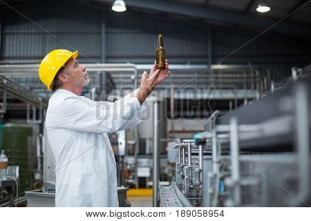 Attentive factory worker examining a bottle in factory