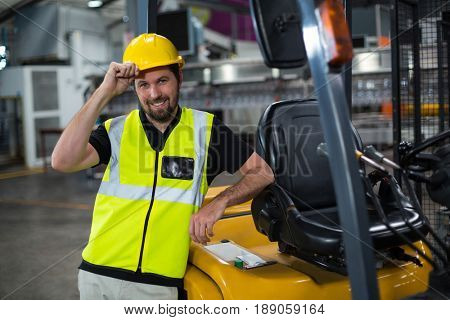 Portrait of smiling factory worker leaning on forklift in factory