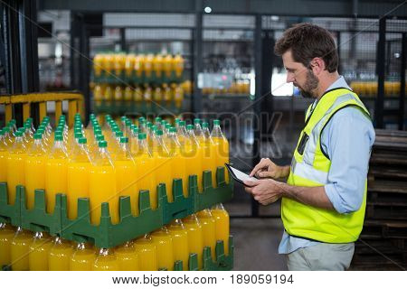 Factory worker maintaining record on juice bottles on digital tablet in factory