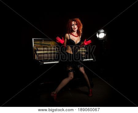 Sexy girl looks like a doll with curly redhead standing next to a piano, on a dark background. Fashion style. From the back highlights the soffit