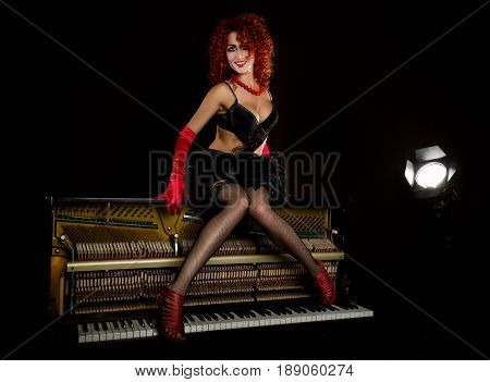 Sexy girl looks like a doll with curly redhead sits on a piano, on a gray background. Fashion style. From the back highlights the soffit