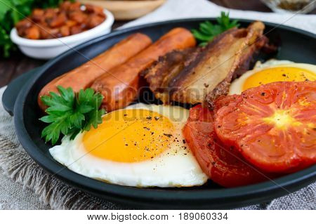 English breakfast: sausages bacon tomatoes egg beans in sauce fried mushrooms toast on a dark wooden background. Close up. Traditional classic food of England.