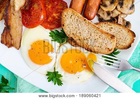 Traditional English breakfast: bacon mushrooms eggs tomatoes sausages beans toast on a white plate on a bright wooden background. England classic cuisine. Close up. The top view