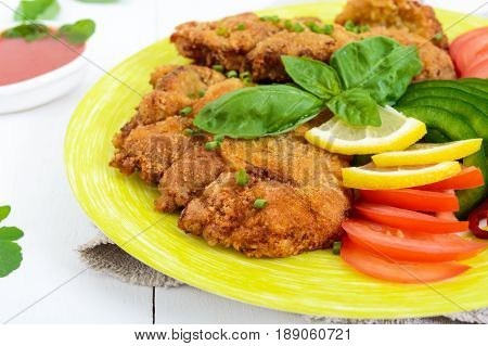 Schnitzel with vegetables tomato sauce on a white wooden background. Close up
