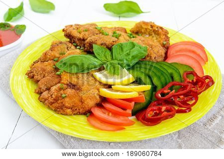 Schnitzel with vegetables tomato sauce on a white wooden background.