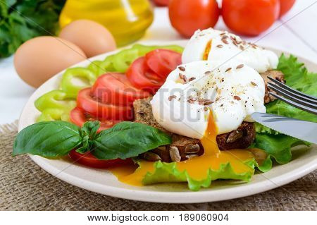 Sandwich with egg poached lettuce black bread with seeds tomatoes sweet pepper on a plate on a white wooden table.