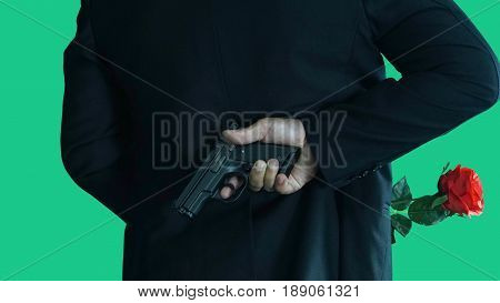 Businessman isolated on green screen with studio lights. A man in black suit with a red rose and a gun in hands. The beauty killer in business game.