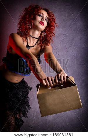 Curly redhead sexy girl looks like a doll holds a cardboard box on a gray background. poppet for adult men. Fashion style.