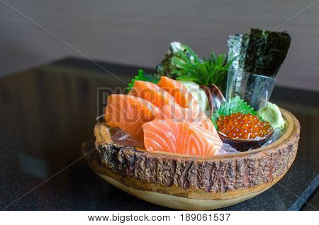 fresh salmon sashimi with salmon ikura or salmon egg and sheet of dried seaweed in bowl set on table Japanese food selective focus