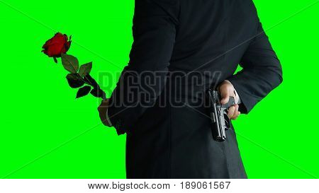 Businessman isolated on green screen. A man or killer in black suit with a black gun in and a red rose his hands.