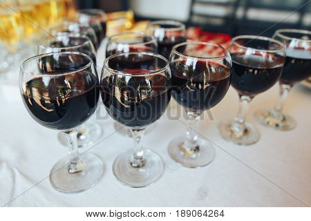 Many glasses of red wine in a row on the table