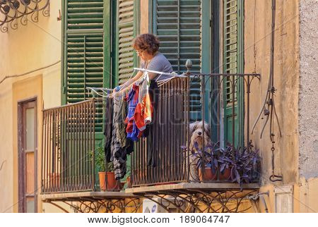 A woman is hanging the laundry on the balcony while her dog keeps an eye on the busy street below - Via Porta di Castro Palermo Sicily Italy, 20 October 2011