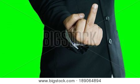 Angry or furious businessman isolated, green screen. A man in black suit show middle finger, fuck you off sign.