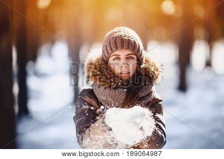 Close-up portrait of young beautiful happy smiling girl wearing stylish knitted winter hats, mittens, scarf yoke. Daylight - sunset and glare. He looks at the camera. Toned