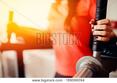 Girl doing muscle press exercise. in the gym. hands close-up.  hign contrast and monochrome color tone