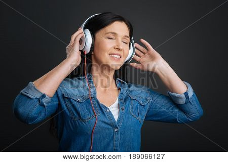 Expressing oneself through hobby. Graceful pretty emotional woman having the headphones on and enjoying amazing song while closing her eyes