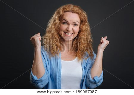 This is fascinating. Cute admirable emotional lady looking enthusiastic while making expressive gestures and standing isolated on grey background