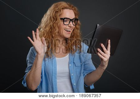 Borderless communication. Cute friendly excited woman using modern technology for being in touch with her acquaintances from all over the world and talking online