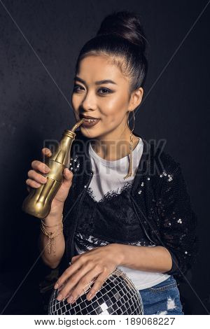 Glamour Asian Disco Girl With Golden Bottle And Disco Ball Smiling And Looking At Camera Isolated On