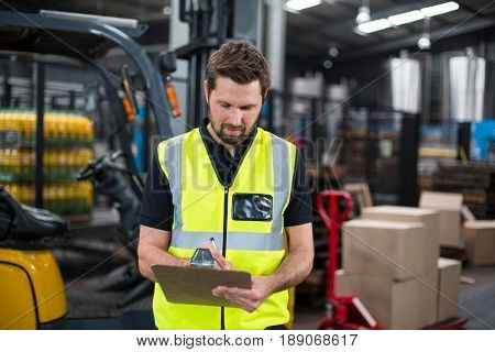 Attentive factory worker writing on clipboard in factory