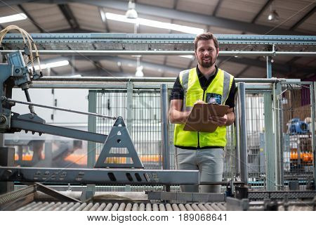 Smiling factory worker writing on clipboard in factory