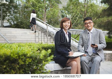 Chinese business people sitting outdoors