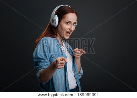 Cool gal. Cool young red haired woman behaving goofy while moving to her favorite track and having her headphones on