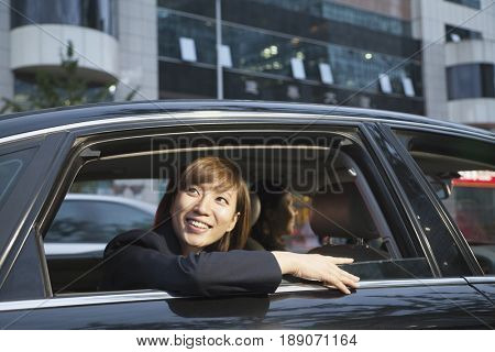 Chinese businesswoman looking out of car