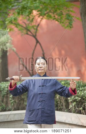 Older Chinese man practicing taiji in park