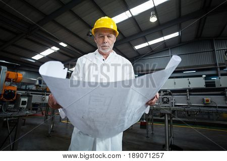 Factory engineer looking at blueprint in bottle factory
