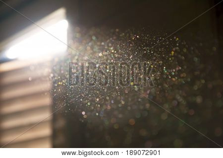 A ray of sun coming through the wooden shutters illuminates dust on the inside of a dark room. Close up selective focus. Vintage background.