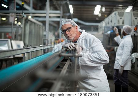 Factory engineer monitoring production line in drinks production plant