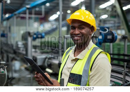 Portrait of smiling factory worker using a digital tablet in the factory