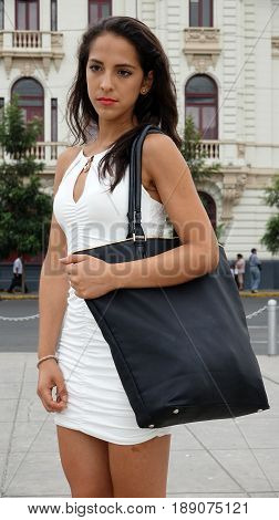 Hispanic Female With Pocketbook Wearing A White Dress