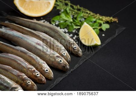 Fresh Sea Fish Smelt Or Sardines Ready For Cooking With Lemon, Thyme, And Coarse Sea Salt On A Black