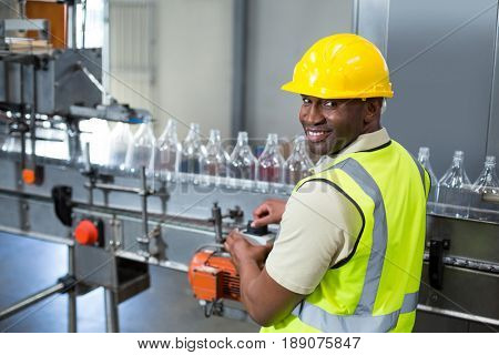 Smiling factory worker operating machine in drinks production plant