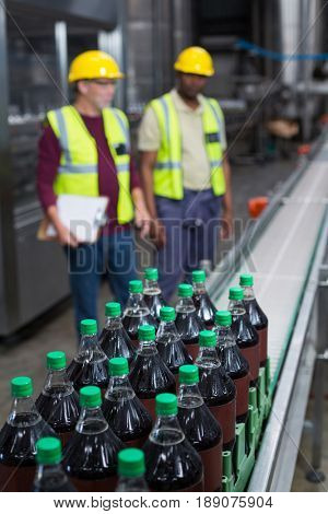 Crate of cold drink bottles moving on the production line at drinks production plant