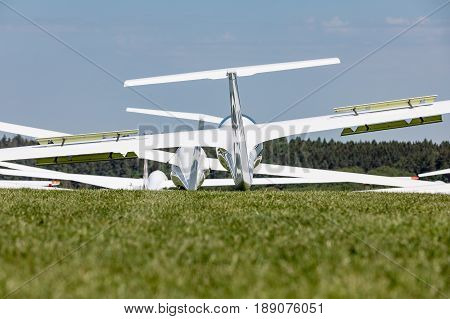 Glider on the grassy airfield in sunny day.