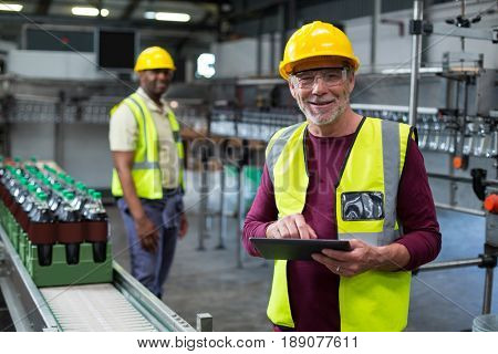 Smiling factory worker with digital tablet standing near the production line at factory