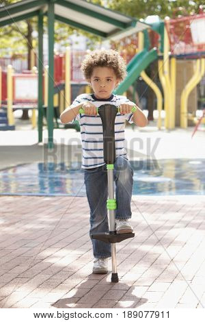 Mixed race boy holding pogo stick at playground