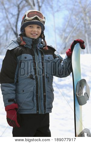 Caucasian boy with snowboard in snow