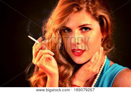 Woman smokes marijuana. Girl with seductive eyes who smokes cigarette. Smoke is bad habit. Nicotinic acid is harmful to health and female beauty.
