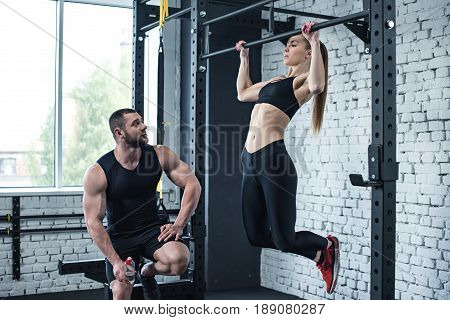 Sportswoman Doing Pull Up While Trainer Looking At Her In Sports Center