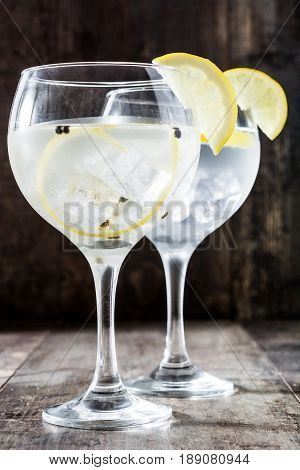 Glass of gin tonic with lemon on wooden background